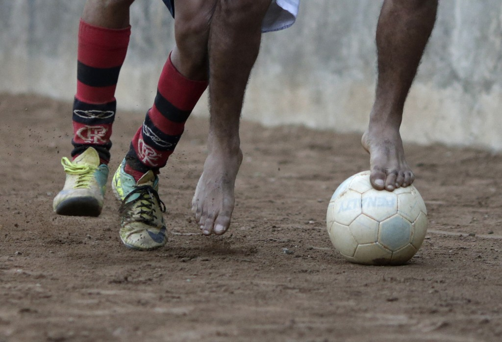 "Players battle for the ball during a Sunday ""pelada"" soccer match in the Borel favela of Rio de Janeiro, a World Cup host city, May 4, 2014. Sunday soccer is a decades-old tradition when Brazilians of all walks of life play on the beaches, in the slums, and on the streets matches that are known as ""peladas"" or ""naked"". Pelada can refer to a street match where everyone plays barefoot with ÒnakedÓ feet, or a match on a grassless ÒnakedÓ field, or a match with a ball so worn that it is Ònaked.Ó With the 2014 World Cup just one month away, people of all walks of life in the host cities are spending their Sundays practicing the sport for which their country is about to become the global stage. The tournament will take place in Brasilia, Belo Horizonte, Rio de Janeiro, Sao Paulo, Natal, Fortaleza, Salvador, Porto Alegre, Curitiba, Cuiaba, Manaus, and Recife. Picture taken May 4, 2014. REUTERS/Ricardo Moraes (BRAZIL)"